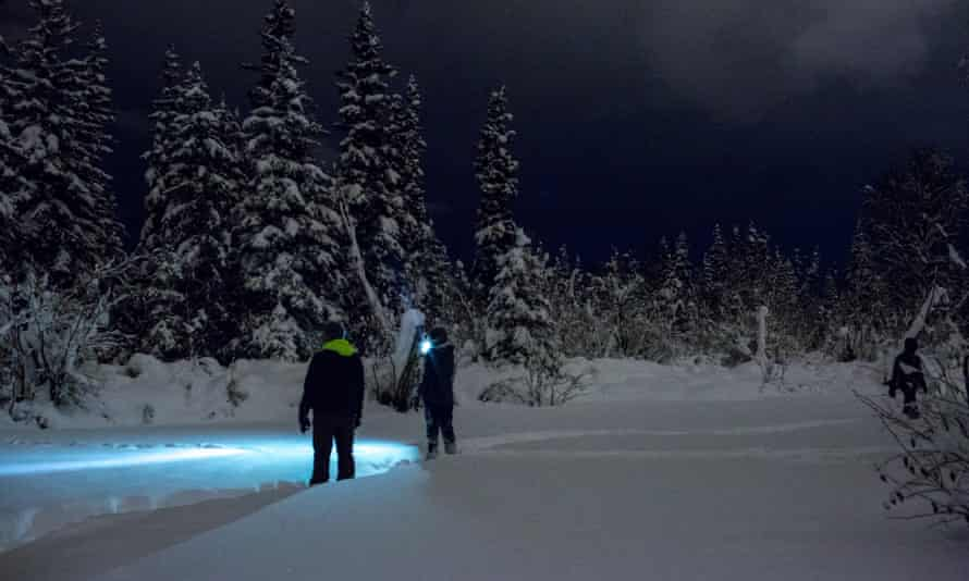 Two airmen investigate tracks in the snow during the homeless count in Anchorage in the early morning hours.