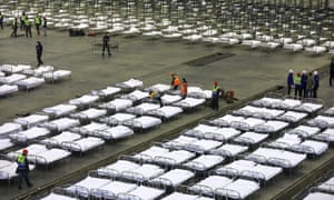 Workers arrange beds in a convention centre that has been converted into a temporary hospital in Wuhan.