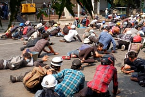 Protesters lie on the ground after police opened fire to disperse an anti-coup protest in Mandalay.