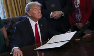 President Trump signing an executive order in the White House Oval Office.