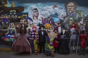 A group of people dressed up for the Day of the Dead parade pose in Oaxaca.