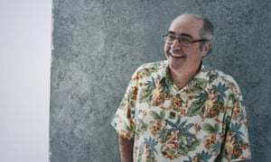 Danny Baker standing, in a Hawiian shirt, hands in pockets, smiling