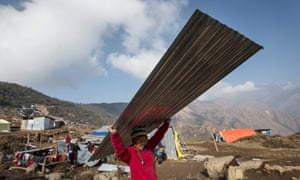 A woman carries a metal roof panel to rebuild her damaged house in Laprak, in Nepal's Gorkha district.
