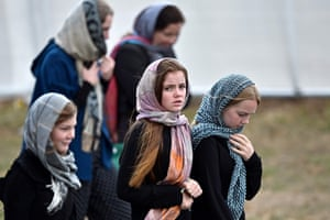 Residents and schoolchildren wearing headscarves arrive for the funeral for some of those killed in New Zealand's twin mosque attacks at Memorial Park cemetery in Christchurch.
