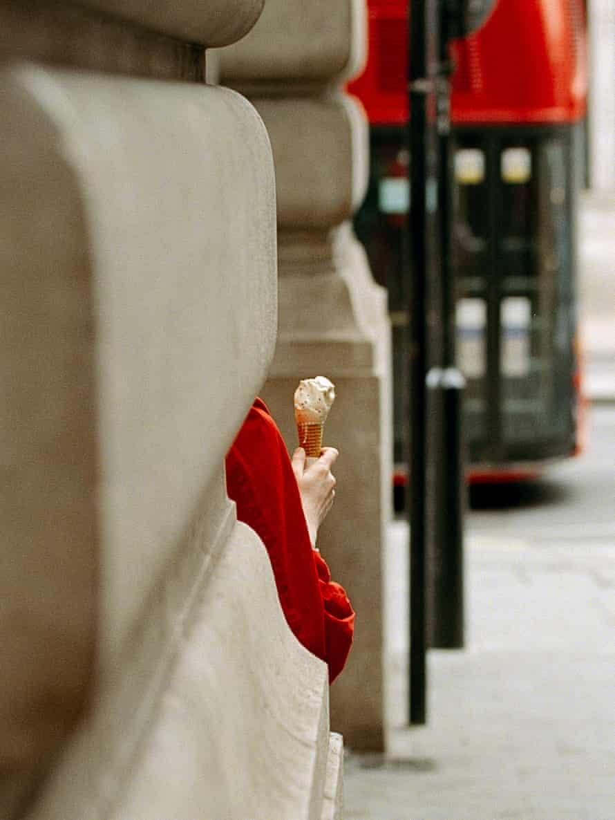 A pedestrian with an ice-cream at Piccadilly Circus.