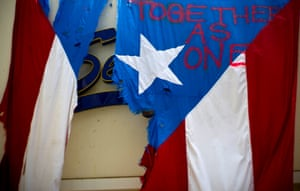 """damaged Puerto Rican national flag spray painted with the words """"Together as One"""" hangs from the facade of a business, in San Juan, Puerto Rico."""