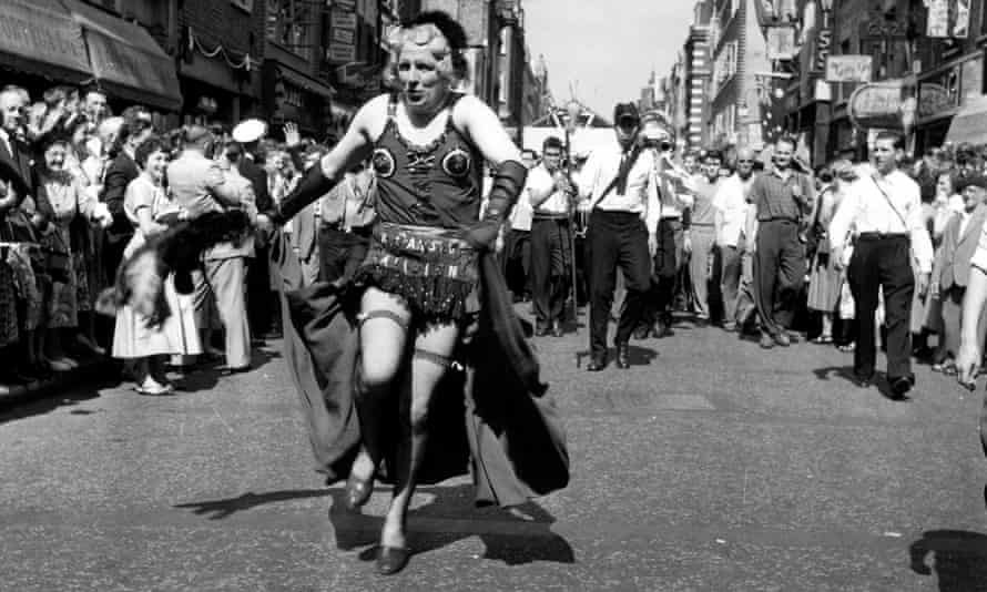 A man in drag heads a carnival procession down Old Compton Street during the Soho Fair in 1965
