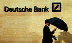 A man with an umbrella walks past Deutsche Bank offices in London