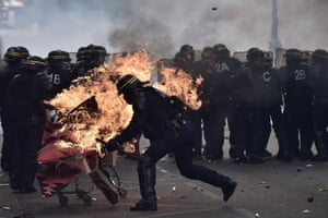 Paris, France Anti-riot police officers try to push away a burning trolley launched towards them
