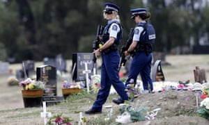 Armed police patrol a cemetery near Muslim graves in Christchurch.