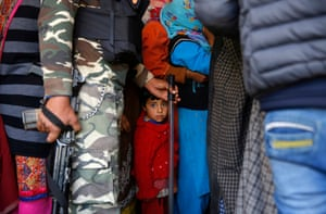 A child looks on as Kashmiri voters queue at a polling station