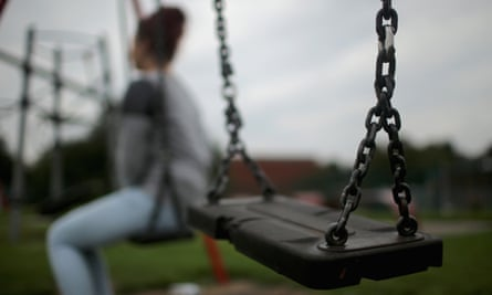 A teenage girl poses on a swing