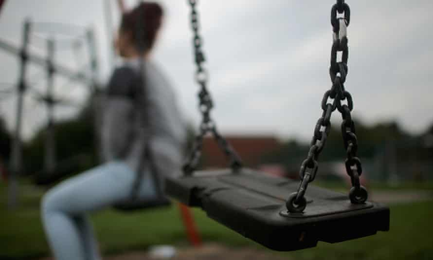 An anonymised teenage girl sitting on a park swing
