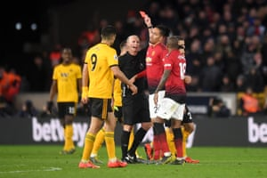 Referee Mike Dean hands out his 100th red card.