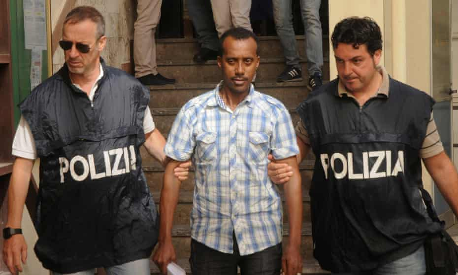 Police accompany one of the suspects in Palermo