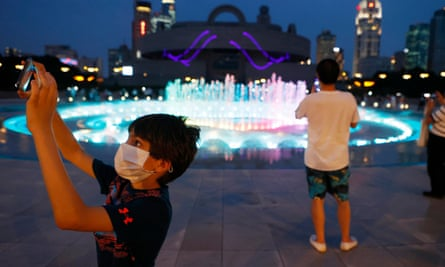 People wearing face masks watch a musical fountain at the People's Square in Shanghai