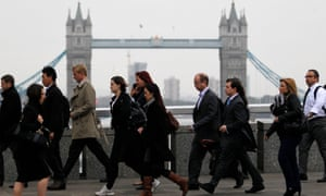 Workers walking across London Bridge on their way to the City of London today