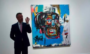 A Sotheby's official stands next to Untitled, a 1982 painting by Jean-Michel Basquiat.