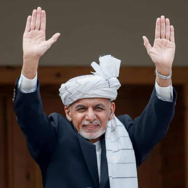 Ashraf Ghani raising both his arms to a crowd