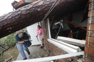 Residents collect belongings from their destroyed home after several uprooted trees fell on the house