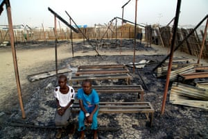 Chubat (right), 12, sits with her friend in the burned ruins of her school in Malakal Protection of Civilian site. Chubat and her friend used go to the school every day and enjoyed learning new things, especially during their English and maths classes.