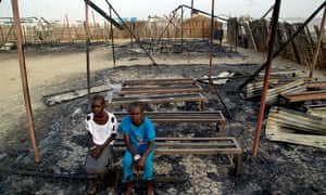 Girls sit amid the ruins of a primary school burned down in fighting at the Malakal protection of civilians site in South Sudan