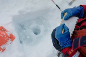 The UNCW technician Dave Wells makes notes next to a hole drilled in an ice floe.
