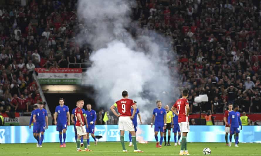 Players wait after a flare was thrown on the field following England's third goal