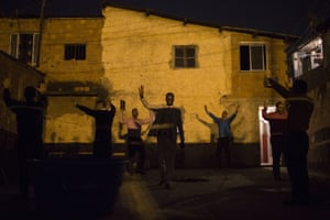 Pastor Nilton, back right in blue, rejoices with members of his church after learning that residents will allow him to hold a prayer service in their courtyard, in a gang-ruled slum in Rio de Janeiro