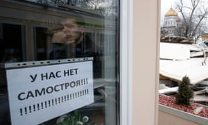A man looks out of a window with a sign reading 'Ours isn't a self-built building!' amid demolition of illegal street kiosks and stalls near the Krapotkinskaya metro station