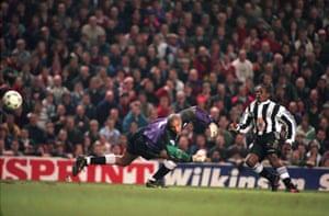 Faustino Asprilla scoring past Liverpool goalkeeper David James in 1996.