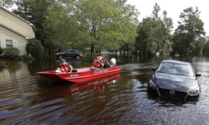 Members of the US Coast Guard check on a flooded neighborhood in Lumberton, North Carolina Monday.