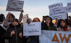 "Demonstrators protest outside the Amazon fulfillment center in Shakopee, Minnesota, on 14 December. ""If you get injured, they don't treat you well, they don't care,"" said employee 24-year-old Hibaq Mohamed."
