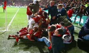 Korey Smith is mobbed by Bristol City players and fans after scoring their late winner against Manchester United.