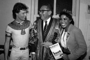 Former secretary of state Henry Kissinger, centre, tries on singer Andy Gibb's dreamcoat backstage at the Royale theatre in New York, in 1982 alongside Gibb, left, and co-star Sharon Brown, right