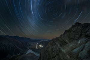Above the World Lee Cook (UK) Taken from Sefton Bivouac, the oldest hut in Mount Cook National Park, New Zealand, star trails spiral over the majestic mountains of the park and the seemingly peaceful village below.