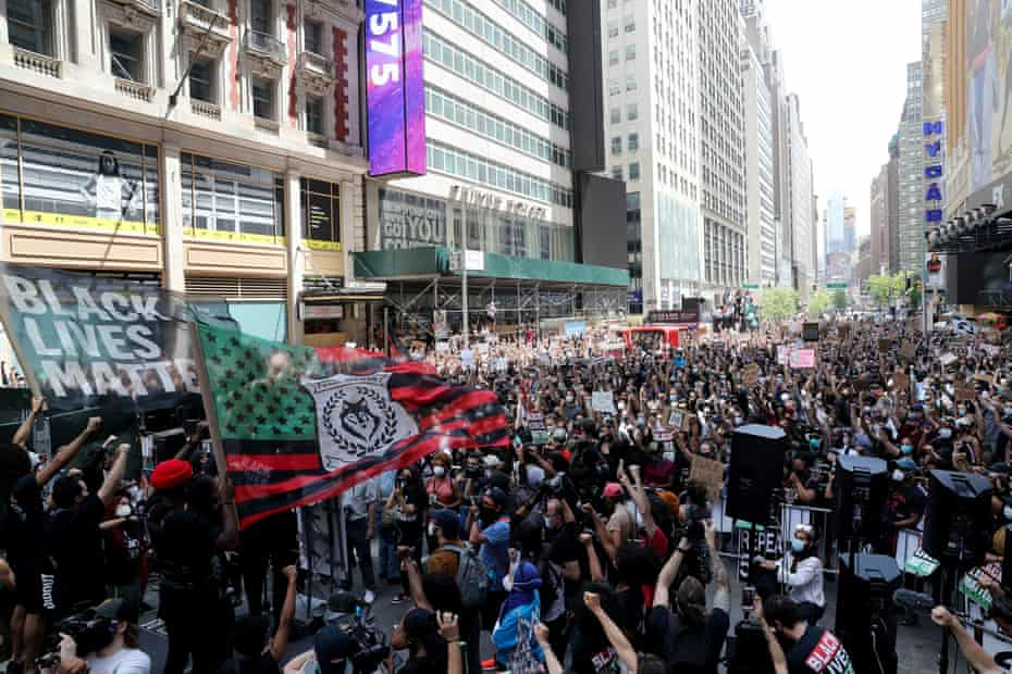 Demonstrators raise their fists at Times Square during a protest on Sunday.