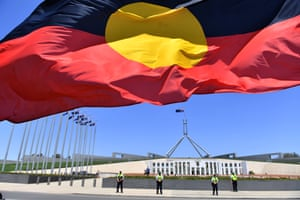 An Aboriginal flag flies as an Invasion Day rally descends on Parliament House in Canberra.