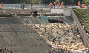 Engineers and members of the emergency services inspect the damaged spillway of the Toddbrook reservoir dam