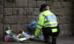 A police officer places floral tributes near the building site.