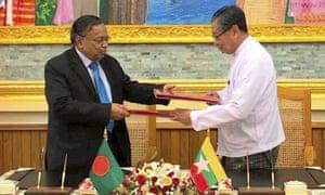 Bangladesh's Abdul Hassan Mahmud Ali and Myanmar's Kyaw Tint Swe exchange documents in Naypyitaw, Myanmar