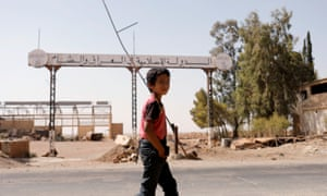 A boy walks past a sign that reads 'Islamic State in Iraq and Syria' in Raqqa.