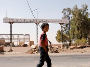 A boy walks past a sign that reads 'Islamic State in Iraq and Syria' in Raqqa, Syria, 20 August