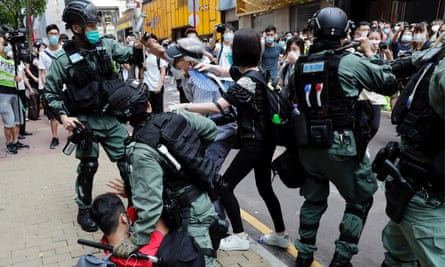 Anti-government demonstrators scuffle with riot police during a lunchtime protest in Hong Kong