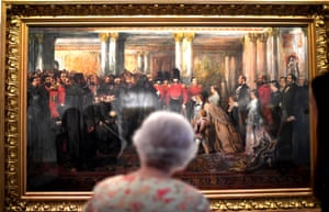 London, EnglandQueen Elizabeth II looks at a painting of Queen Victoria inspecting wounded Coldstream Guardsmen, 1855, by John Gilbert, as part of the exhibition to mark the 200th anniversary of the birth of Queen Victoria for the Summer Opening of Buckingham Palace.