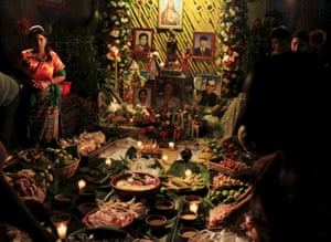 El Salvador: A girl stands at a family altar where offerings have been laid for the All Saints' Day celebration, known as Festival de los Canchules, in Nahuizalco