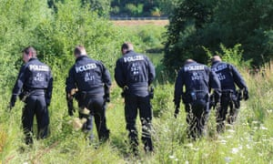 Police officers search for evidence near the crime scene in Würzburg, Germany