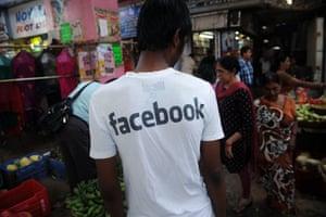 A young man Indian wearing a Facebook T-shirt at a market in Mumbai.