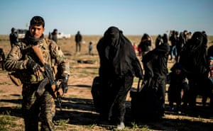 Women and children walk with their suitcases as they are directed by members of the Kurdish-led Syrian Democratic Forces (SDF) after leaving the Islamic State (IS) group's last holdout of Baghouz
