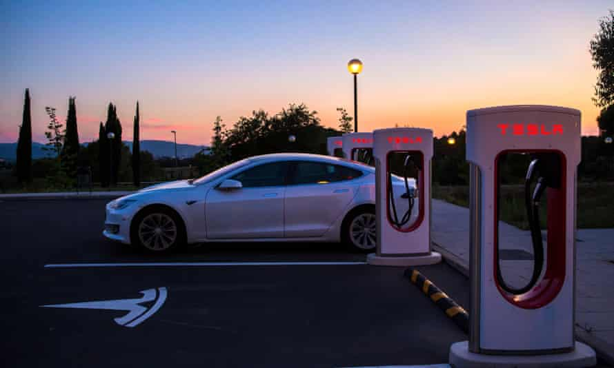 A Tesla Model S charges at a charging station.